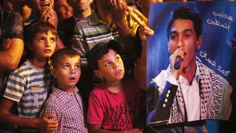 A Palestinian holds a poster of singer Assaf as the crowd watch the result of <i>Arab Idol</i> in Ramallah, West Bank.
