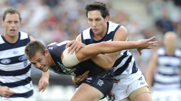 Geelong's Harry Taylor keeps the pressure on Port Adelaide's Paul Stewart.