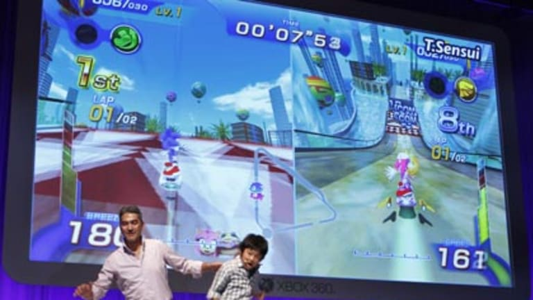 Microsoft Japan's Home & Entertainment General Manager Takashi Sensui, left, and a model boy demonstrate Microsoft's Kinect motion-sensing system.