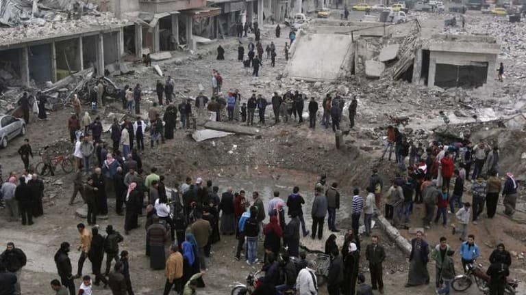 Residents inspect a huge hole in the ground at a site hit by what activists say was a Scud missile from forces loyal to Syria's President Bashar al-Assad.