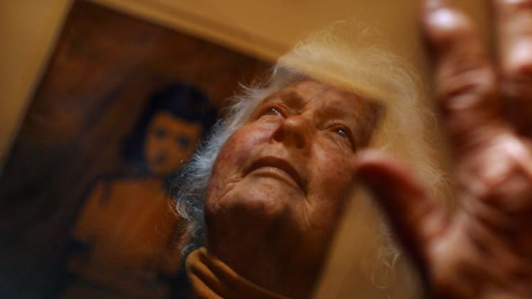 Betty Burstall photographed in 2005 with a painting by artist Charles Blackman, which he gave her 40 years earlier after she helped him out by paying for his dinner.