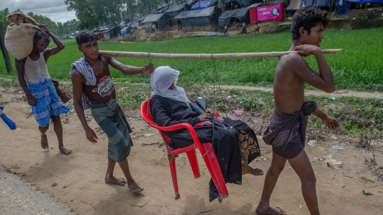 A sick Rohingya Muslim woman, Amila Khatoon, is carried on a plastic chair, by her sons on the way to hospital outside the refugee camp in Bangladesh.