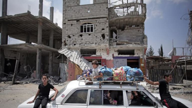 Palestinians in a car with their belongings drive past a destroyed house in Rafah's district of Shawkah in the Gaza Strip.