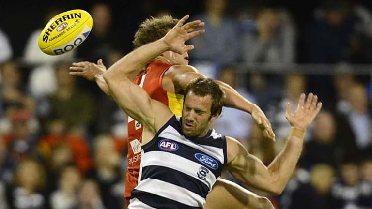 Back to back: Cat Joel Corey and his Gold Coast opponent momentarily lose sight of the football last night.