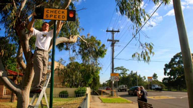 """""""It's not just for the safety of the kids, it's also for fairness on drivers''...Peter Olsen installs a sign near Cartwright Public school."""
