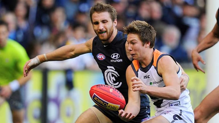 Under pressure: Toby Greene gets some close attention from Carlton's Zach Tuohy.