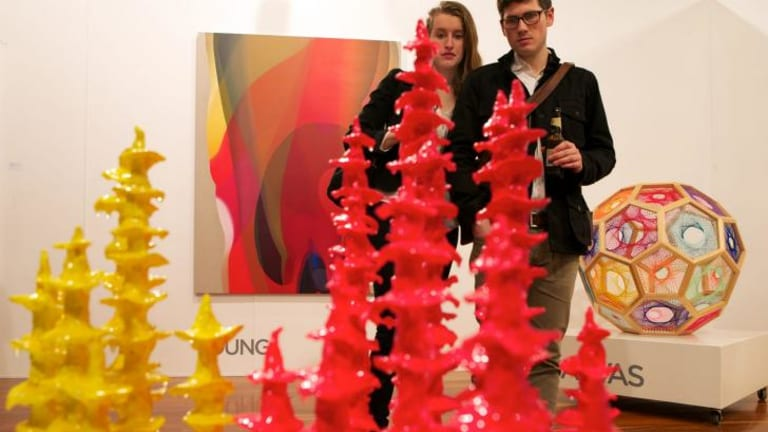 A couple looks at a Tracy Sarroff piece at the Arc One gallery stand.