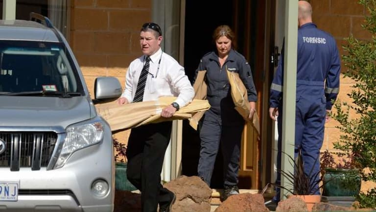 Detectives and forensic officers carrying evidence from the victim's house.