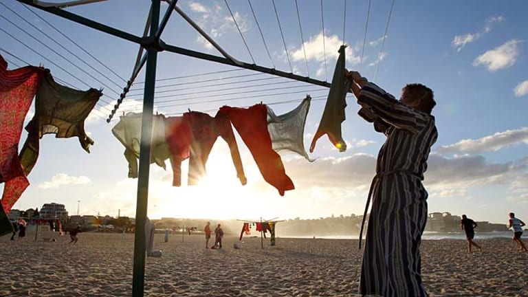 Coming out in the wash . . . a woman hangs up washing on Bondi Beach as part of a surreal artwork representing the impact of encroaching urbanisation on the Aussie backyard.