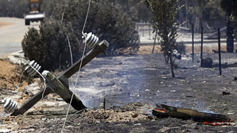 A burnt down power pole sits on the side of the road after a bushfire tore through Toodyay.