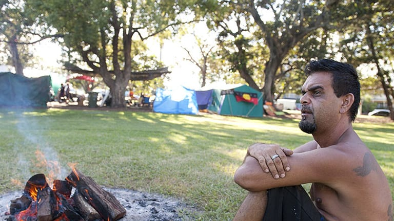 Jason Harrison sits near the Sacred Fire at the Musgrave park tent Embassy, Brisbane, on March 31.