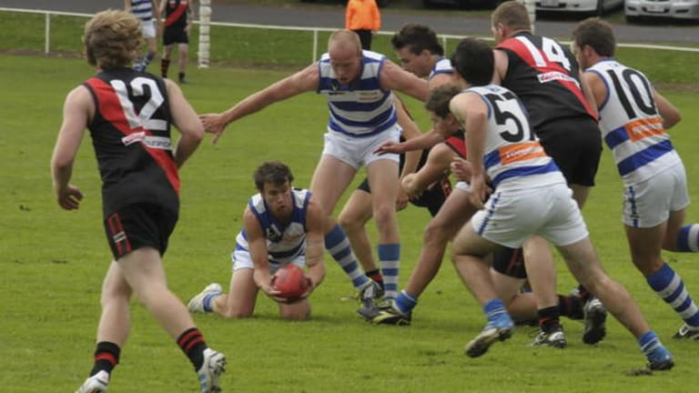 Casterton captain Dylan Ryan attempts to find a teammate with a handball.