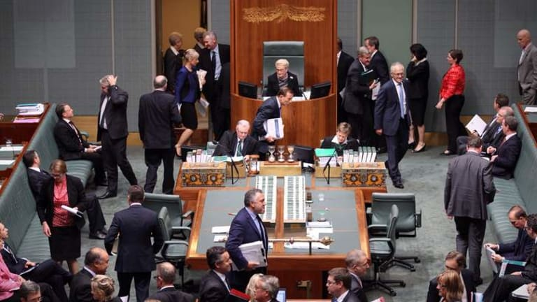 Prime Minister Tony Abbott bows as he votes on a procedure division to deny the opposition a no confidence motion against Madam Speaker Bronwyn Bishop.