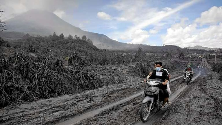 Motorcyclists passing through an area covered by ash as they are evacuated.