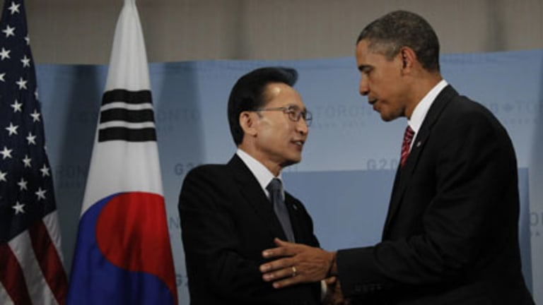 Signal to the North ... Lee Myung-bak, left, greets Barack Obama on the sidelines of the G20 summit.