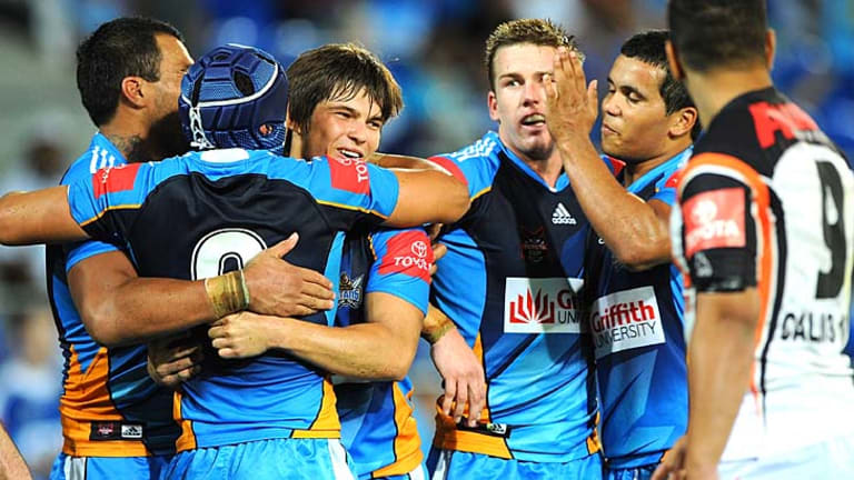 Titans players celebrate after a try on their way towards a comeback victory over Wests Tigers.