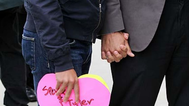 A same-sex couple holds hands while they wait to hear the ruling on Prop 8 outside of the Philip Burton Federal building in San Francisco