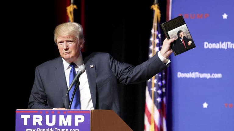 Donald Trump holds up a copy of his 1987 book, Trump: The Art of the Deal.