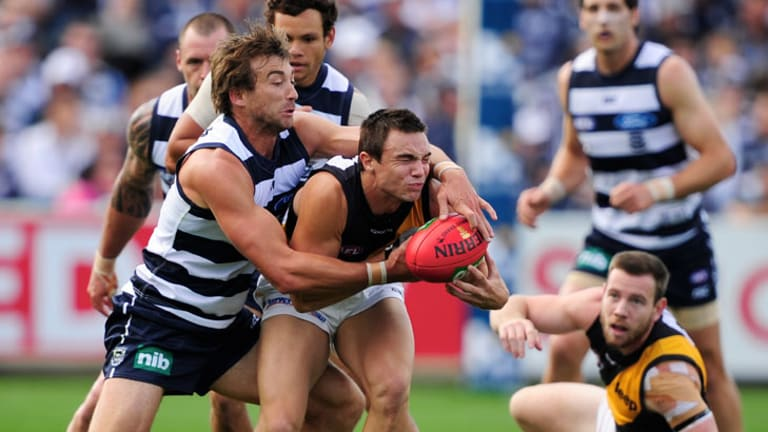 Geelong's Corey Enright lays a tackle on Richmond's Addam Maric at Simonds Stadium.