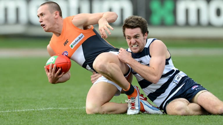Giant tackle: Cat Jesse Stringer brings Tom Scully to his knees.