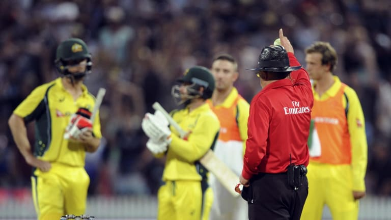 Umpire Ian Gould raises his finger after a video review of a caught and bowled appeal by New Zealand's Matt Henry of Australia's Mitchell Marsh.
