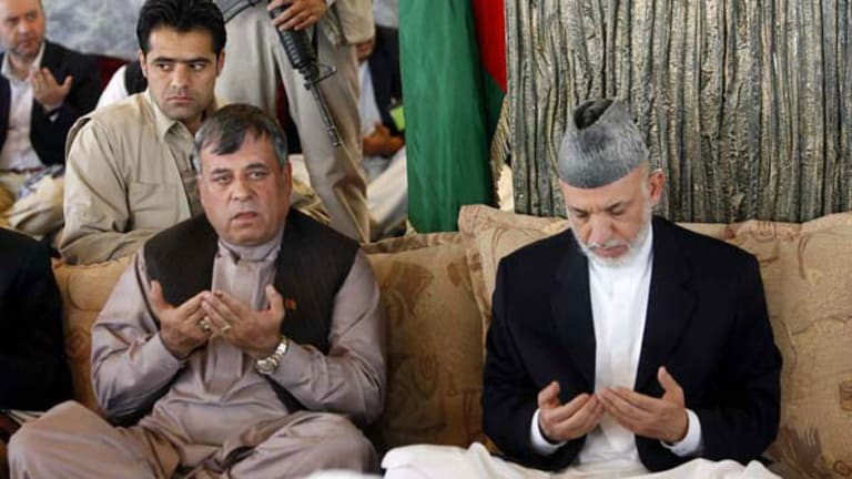 Afghan President Hamid Karzai (right) and Kandahar governor Toryalai Wesaw pray during a visit by the President to the Arghandab district of Kandahar.