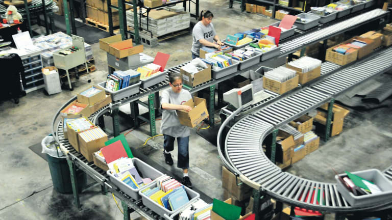 Workers prepare books for shipment in a US-based Amazon warehouse
