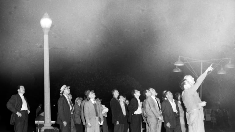 A crowd in Hyde Park, Sydney, tracks the Russian satellite, Sputnik I, as it travels across the night sky, 9 October 1957.