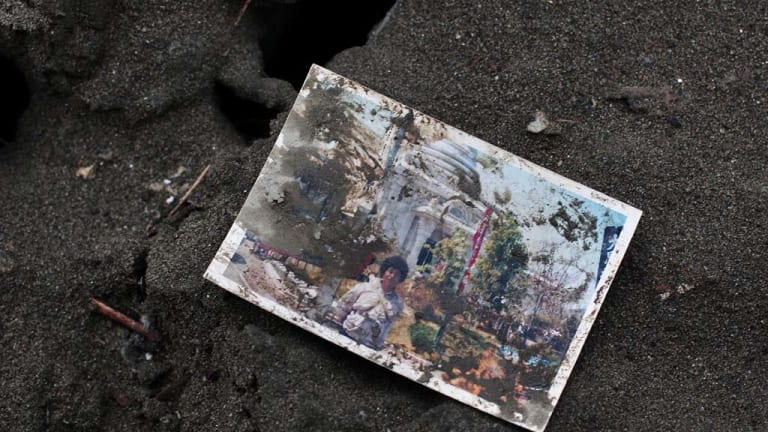 A family photograph is seen amongst the rubble  in Rikuzentakata, Japan..