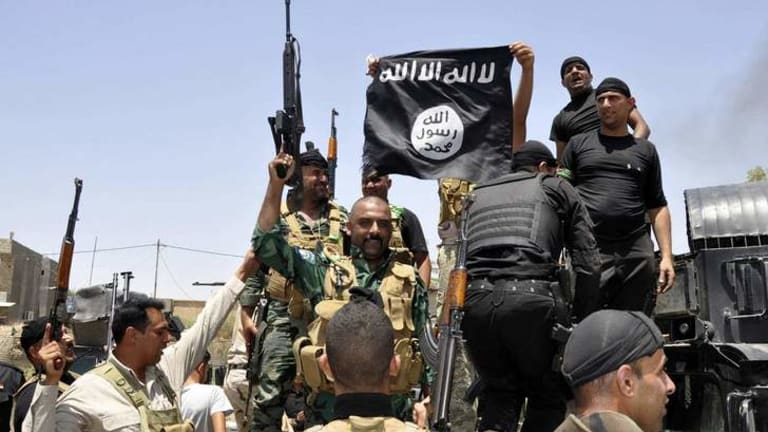 Iraqi security forces pull down a flag belonging to Sunni militant group Islamic State of Iraq and the Levant (ISIL). An Australian suicide bomber fighting with ISIL has reportedly killed three people in Baghdad.