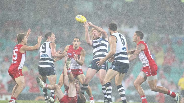 Sydney and Geelong players tussle for the ball in wet and windy conditions at the SCG.