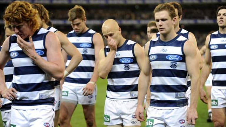 Captain Cameron Ling leads a dejected Gary Ablett and the rest of the Geelong team off the ground after the loss against Collingwood.