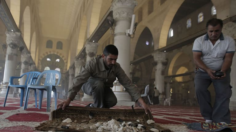 Palestinians clean up debris inside the al-Aqsa mosque on Wednesday following clashes between stone-throwing Palestinians and Israeli securitry forces.