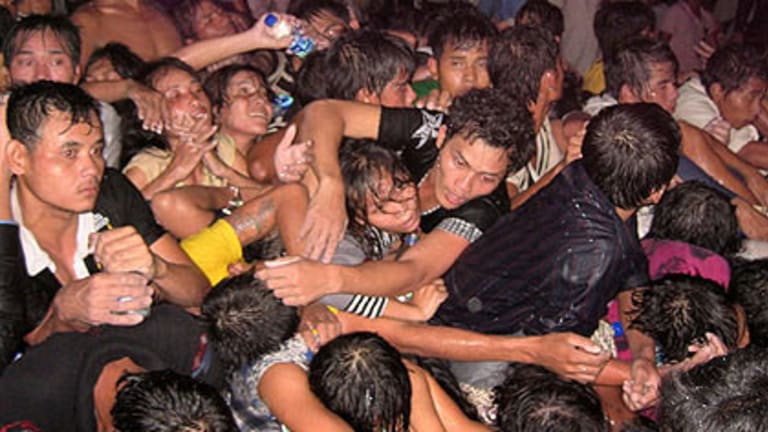 People reach for help from the crush at a water festival that brought millions to Phnom Penh.