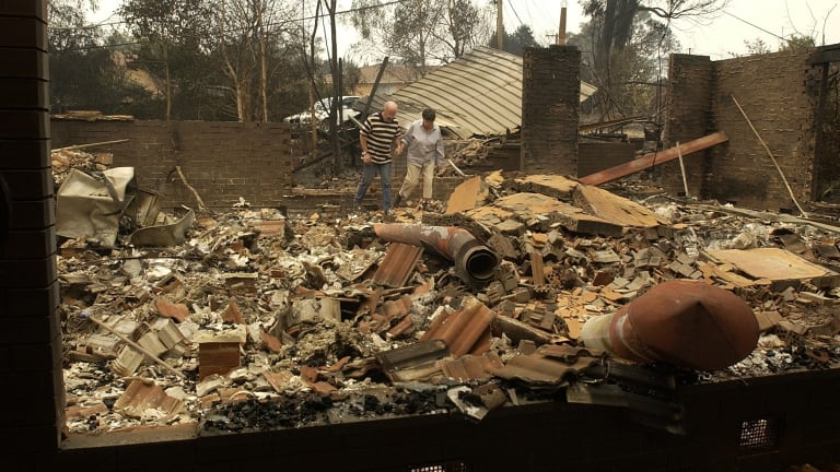 Residents in Duffy walk through the rubble of their home the day after the January 18 firestorm in 2003.