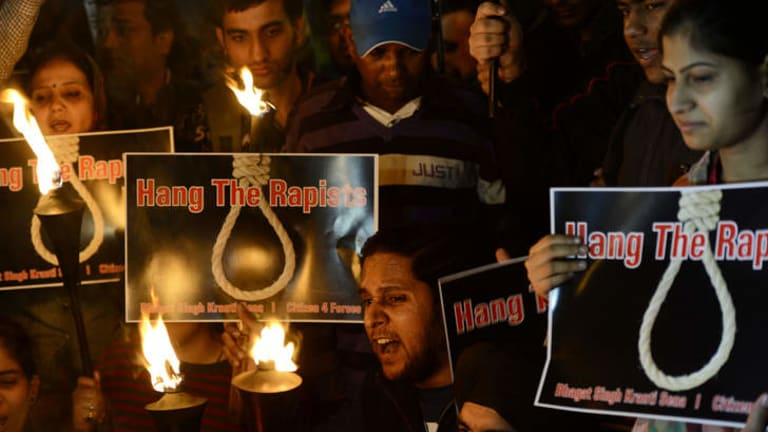 On December 19, 2012 Indian students and activists shout slogans as they carry torches at India Gate during a protest following the gang-rape of a student in New Delhi.