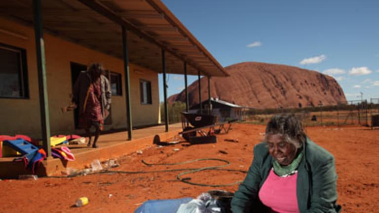 Traditional owner Judy Trigger weaves baskets for tourists with Uluru behind her.