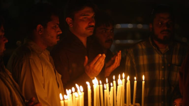 Respect ... people light candles and pray in a memorial service at the scene of the killings in Lahore.