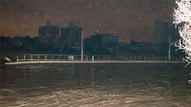 A large piece of the Riverwalk floats down the Brisbane River about 1am on January 13.