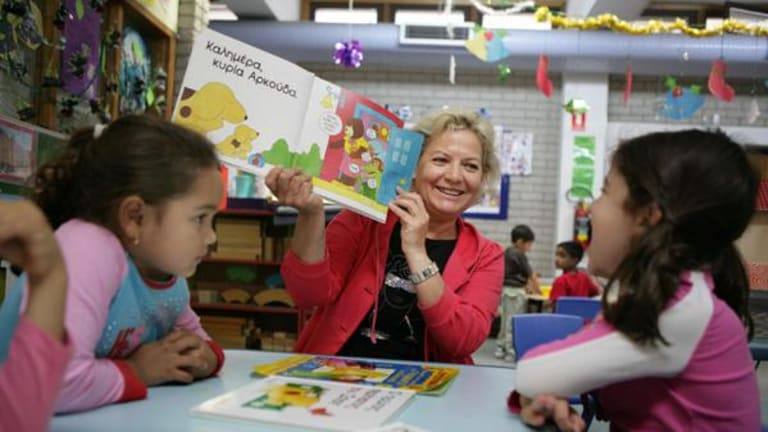 Spot the difference ... Greek teacher Sofia Patala reads to kids at the Greek Orthodox Community of NSW Childcare Centre.