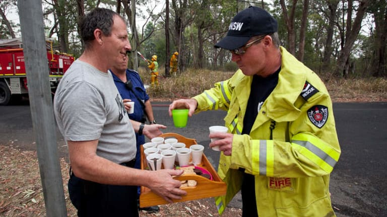 Grateful: A resident offers refreshments to exhausted firefighters and police officers.