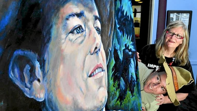 """Tim the Yowie Man with a portrait of himself at the Mt Stromlo Observatory Cafe """"Scope"""" , Canberra , created by artist, Barbara van der Linden."""