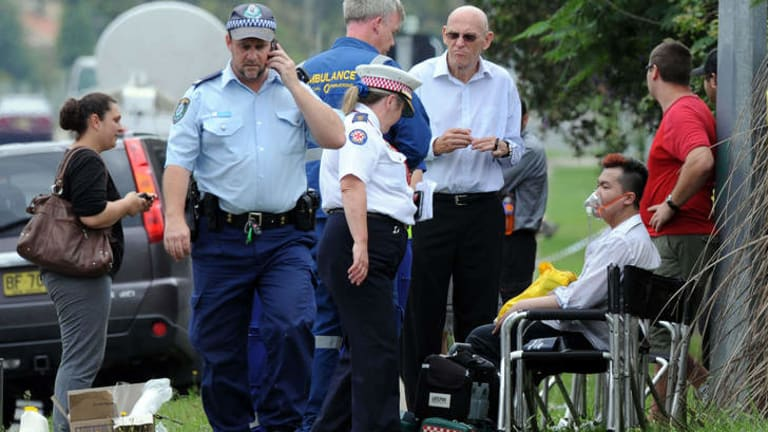 Roger Dean, seated, is given oxygen after a fire engulfed a nursing home.