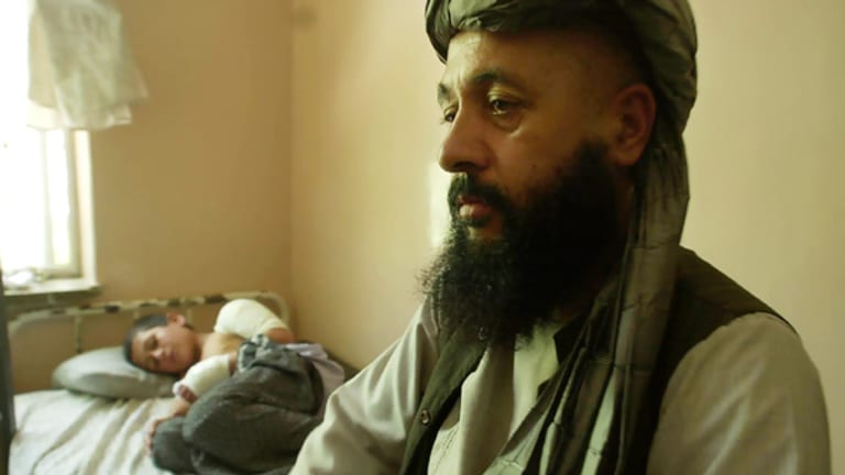 Lawmaker Abdul Khaliq with his injured son, Mohammed Yousaf, 9, at the Kandahar Hospital in southern Afghanistan in July 2006. The attack also killed his brother-in-law, blinded his wife and wounded his daughter.