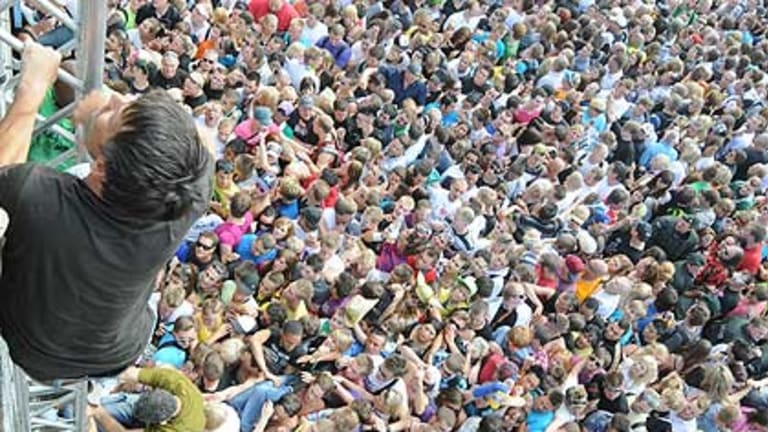 Fans climb out of the crush at the festival after the tragedy.