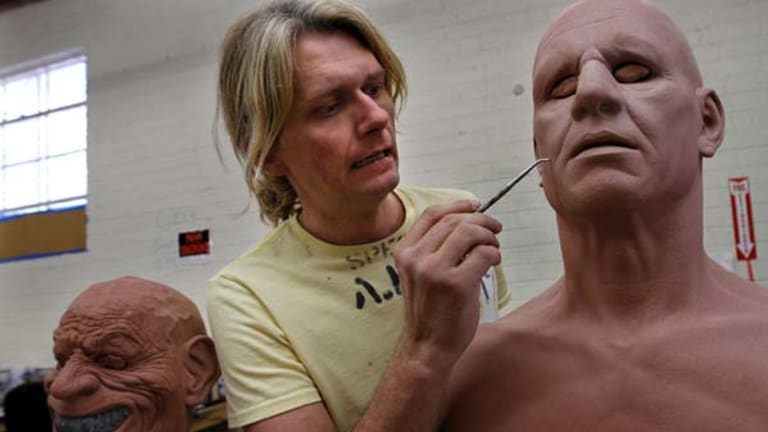 Lifelike ... Rusty Slusser adds skin pores into a form for one of his masks.