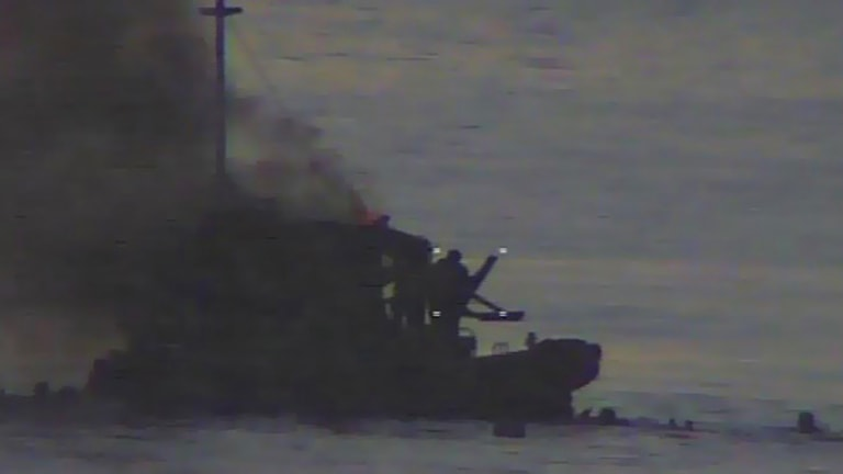 Video footage shows the SIEV 36 on fire and several people in the water.