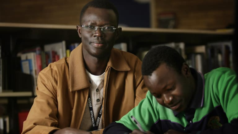 Kot Monoah, a Victoria Police community liason officer, helps Dawoud study.