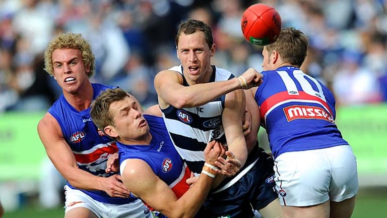 Heavy traffic: Bulldogs (from left) Mitch Wallis, Shaun Higgins and Justin Sherman can't stop Cats onballer James Kelly dishing out  a handball at Skilled Stadium yesterday.