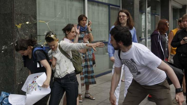 Protest: An Orthodox believer (right) throws an egg at gay rights activists in Moscow.